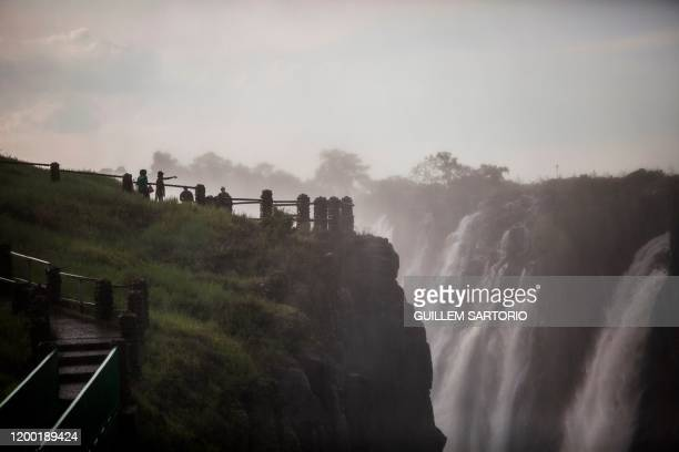Tourists view the majestic Victoria Falls in Livingstone on January 23 2020 The Victoria Falls a UNESCO world heritage site measuring 108 meters high...