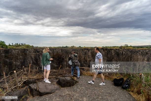 Tourists view the majestic Victoria Falls with a larger part of it without the flowing blanket of water due to a drought in the region Victoria Falls...