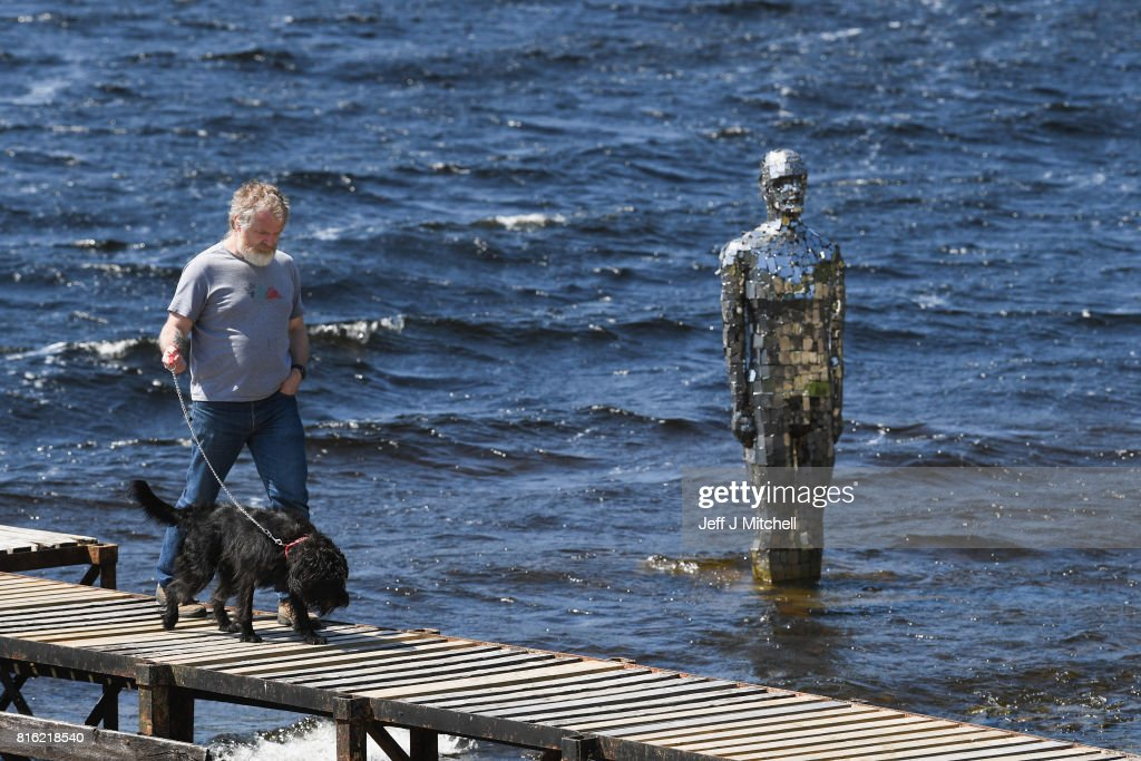 Tourists view the Mirror Man statue by artist Rob Mulholland in Loch Earn on July 17, 2017 in St Fillans, Scotland. The three meter tall sculpture made from mirrored tiles spends the winters out of the water due to the inclement weather, returning again in the summer months.