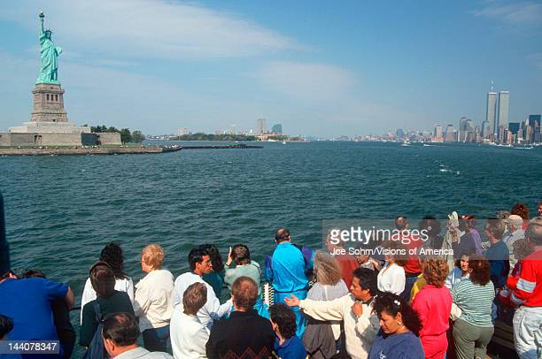 Tourists viewing Statue of Liberty from the Circle Line boat tour of Ellis Island New York New York