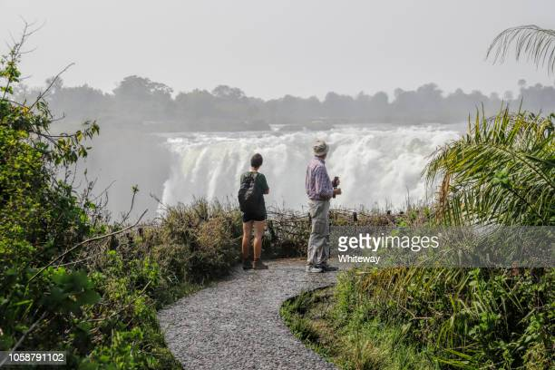 tourists viewing the falls at victoria falls zimbabwe - zimbabwe stock photos and pictures
