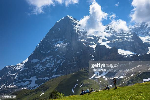 Tourists viewing the North Face of the Eiger from Kleine Scheidegg in the Swiss Alps in Bernese Oberland Switzerland