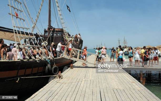 Tourists visit a pirate boat moored at the pink island flamingo on August 2 2010 near Djerba AFP PHOTO / FETHI BELAID / AFP PHOTO / Fethi Belaid