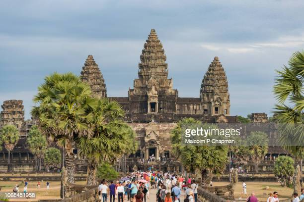tourists visit angkor wat temple at sunset, siem reap, cambodia - angkor stock photos and pictures