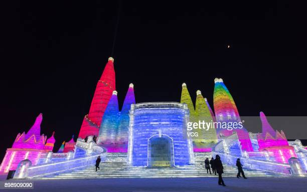 Tourists visit ice sculptures illuminated by coloured lights at Harbin Ice And Snow World part ahead of the 34th Harbin International Ice and Snow...