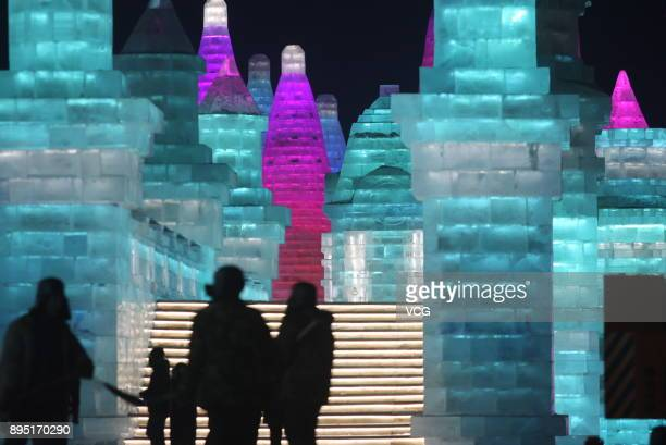 Tourists visit ice sculptures illuminated by coloured lights during the test run of the 19th Harbin Ice And Snow World as part of the 34th Harbin...