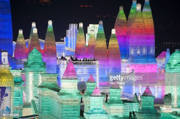 Tourists visit illuminated ice sculptures at Ice and Snow World park on January 4 2018 in Harbin China The Ice and Snow World Park will host the 34th...