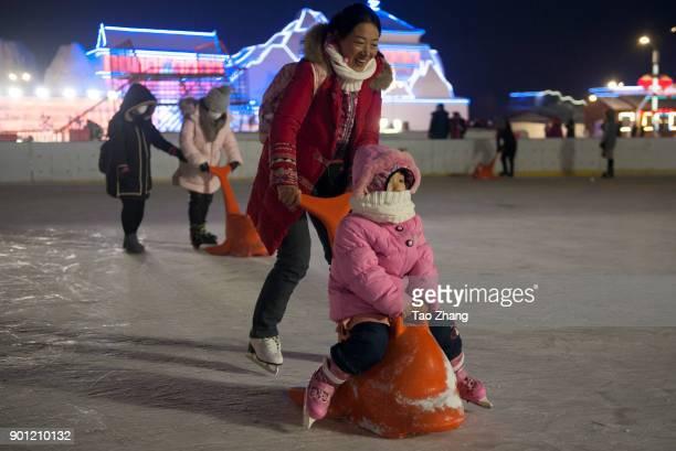 Tourists visit illuminated ice sculptures at Ice and Snow World park on January 4 2018 in Harbin China The Ice and Snow World Park will host the 34th...