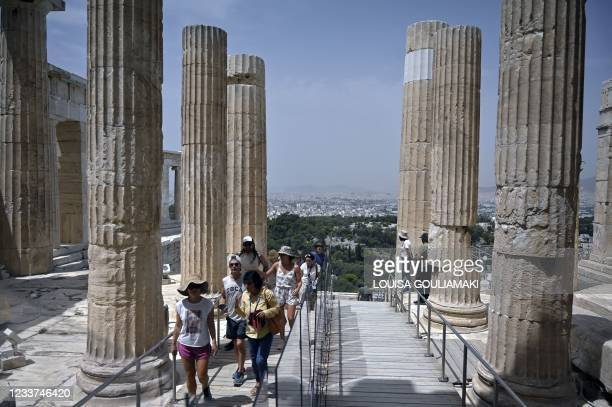 Tourists visit the Ancient Acropolis archeological site in Athens on July 1, 2021 as haze and smog are seen due to the high temperatures. - The...