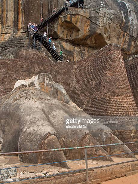 Tourists visit the ancient city of Sigiriya with carvings on a rock in a mountain fortress in Sri Lanka