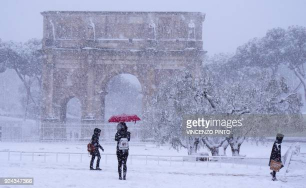 Tourists visit the Arch of Constantine during a snowfall in Rome on February 26 2018 / AFP PHOTO / Vincenzo PINTO