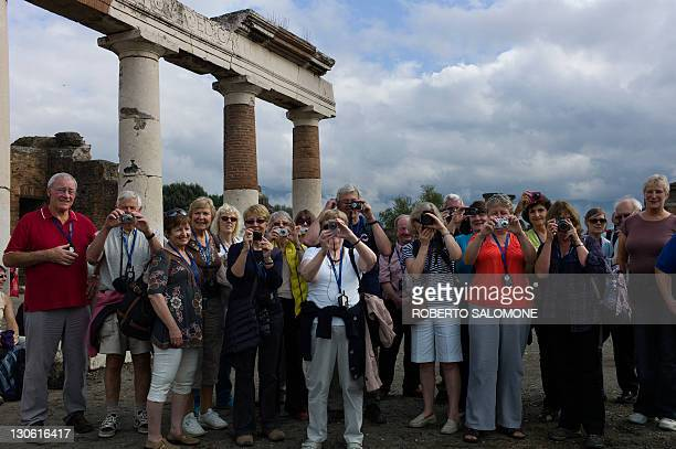 Tourists visit the archological site of Pompei where several Roman walls have collapsed recently following foul weather in southern Italy on October...