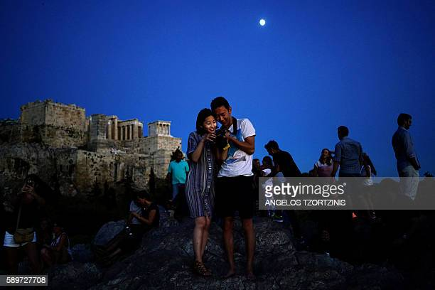 TOPSHOT Tourists visit the Areios Pagos hill with the Acropolis hill in the background in Athens on August 15 2016 / AFP / Angelos Tzortzinis