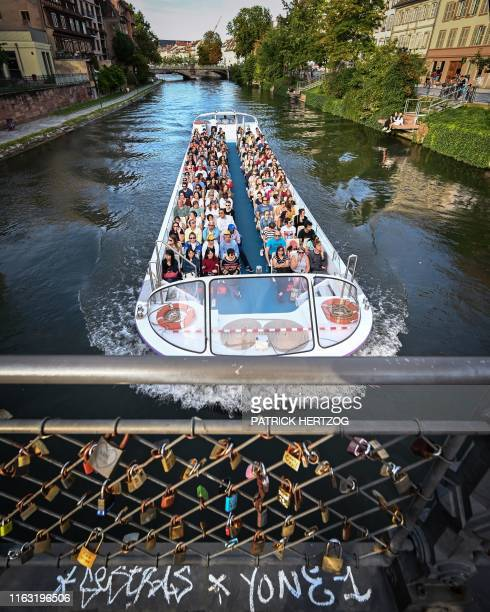 Tourists visit the city on a tour boat sailing along the Ill river, in central Strasbourg, eastern France, on August 22, 2019.