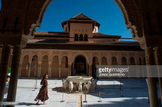 Tourists visit the Court of the Lions at the Alhambra in Granada on June 17 on the day it reopens to the public after three months of closure due to...