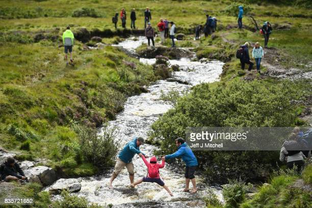 Tourists visit the Fairy Pools on the Isle of Skye on August 18 2017 in Glenbrittle Scotland The Isle of Skye is known as one of the most beautiful...