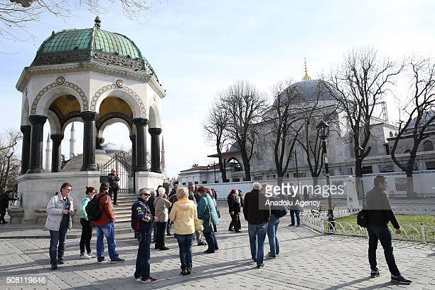Tourists visit the German Fountain at Sultanahmet square in Istanbul Turkey on February 3 2016 Sultanahmet square one of the most attractive...