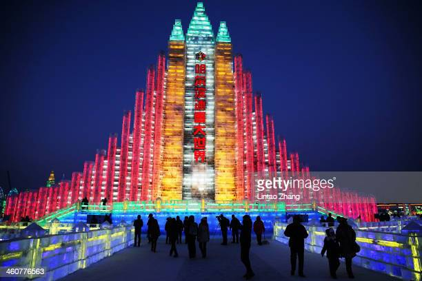 Tourists visit the ice buildings on display at the Grand Ice and Snow World during the 30th Harbin International Ice Snow Sculpture Festival on...