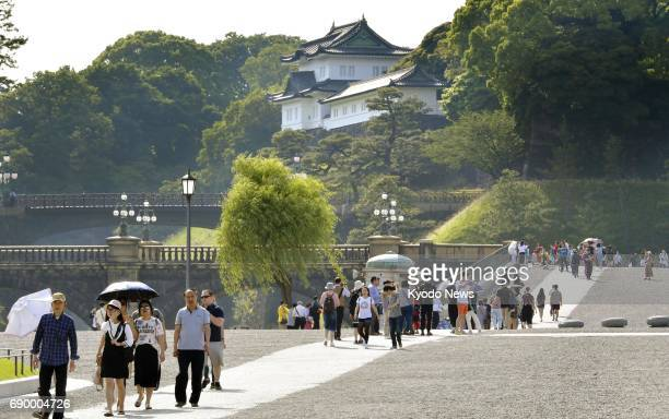 Tourists visit the Imperial Palace in Tokyo on May 30 when Japanese lawmakers agreed to call on the government to launch a debate on enabling...