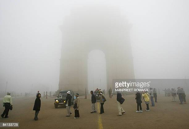 Tourists visit the landmark India Gate in dense fog in New Delhi on December 29 2008 Air and rail traffic was severely hit in the Indian states of...