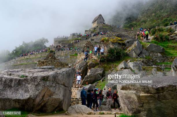 Tourists visit the Machu Picchu complex the Inca fortress enclaved in the south eastern Andes of Peru on April 24 2019
