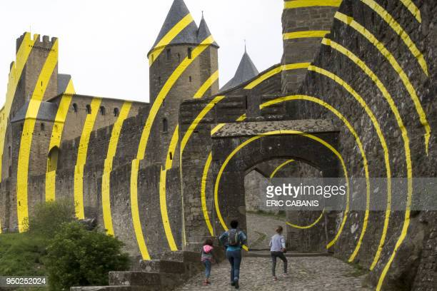 Tourists visit the medieval city of Carcassonne on April 23 whose walls are partly covered with yellow concentric circles created by the Parisbased...