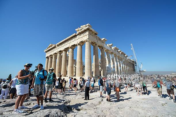 Tourists visit the Parthenon temple on the Acropolis hill in downtown Athens on July 8 2015 Greece's government on July 8 sharply denied a newspaper...