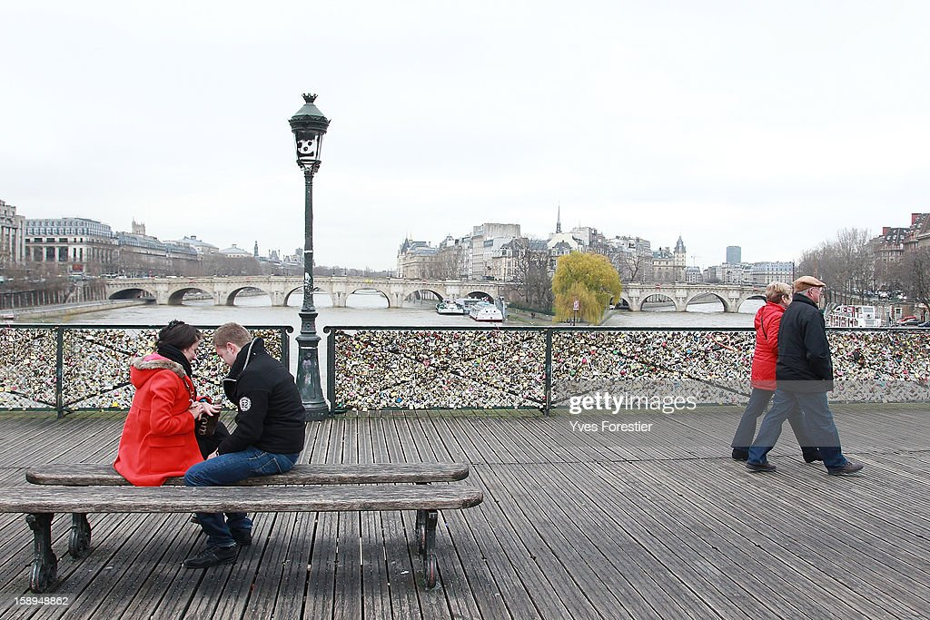 Tourists visit the Pont des Arts on January 4, 2013 in Paris, France. The nine-arch metallic footbridge completed in 1804 is one of the most romantic places of the capital where people visit it to attach love padlocks illustrated with their initials or messages of love, before throwing the key into the River Seine. The bridge is also a meeting place for artists who find inspiration from the surrounding views of the city.