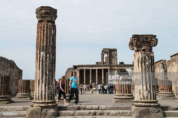 Tourists visit the ruins of the Basilica at the archeological site on April 12 2014 in Pompei Italy The Italian government has enacted a series of...
