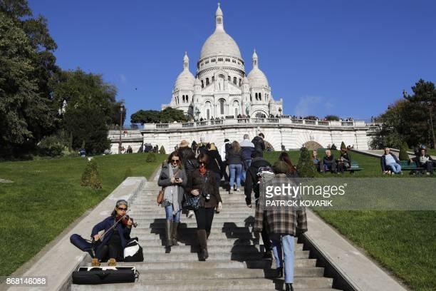 Tourists visit the Sacre Coeur Basilica in the Montmartre district of Paris on October 30 2017 / AFP PHOTO / PATRICK KOVARIK