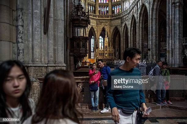 Tourists visit the St Vitus Cathedral on May 9 2016 in Prague Czech Republic Ruler Charles IV began the construction of the St Vitus Cathedral in...