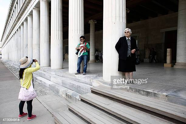 Tourists visit the Stoa of Attalos inside the ancient Agora complex and take a photograph in Athens Greece on Sunday May 3 2015 Greece and its...