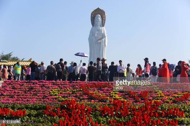 Tourists visit the threesided statue of Guan Yin Buddha on February 16 2018 in Sanya Hainan Province of China The 2018 Chinese New Year which is the...