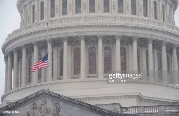 Tourists visit the US Capitol during a snow storm in Washington DC March 21 2018 The fourth Noreaster in less than three weeks Winter Storm Toby is...
