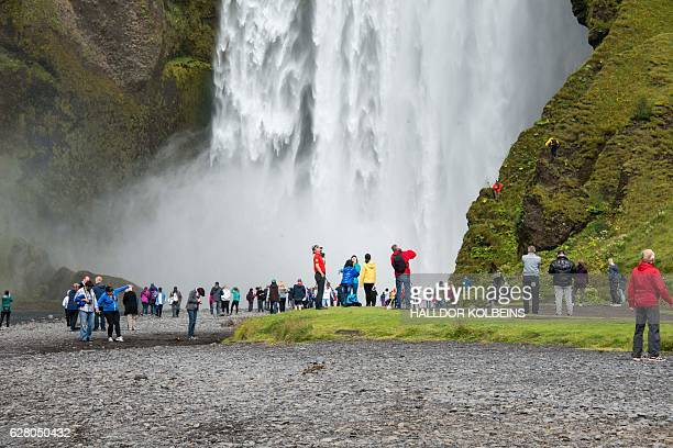 Tourists visit the waterfall at skogar southern Iceland on August 9 2015 An island of ice and lava battered by the Arctic winds Iceland's dramatic...