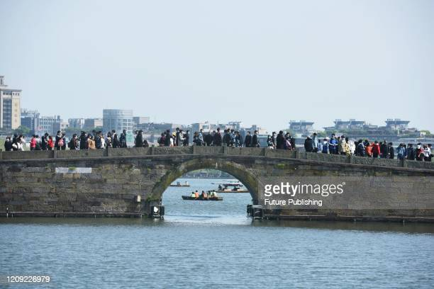 Tourists visit the West Lake park in Hangzhou in east China's Zhejiang province Sunday, April 05, 2020.- PHOTOGRAPH BY Feature China / Barcroft...