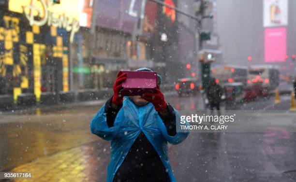 Tourists visit Times Square in New York on March 21 as the fourth nor'easter in a month hits the tristate area on the first full day of spring Winter...