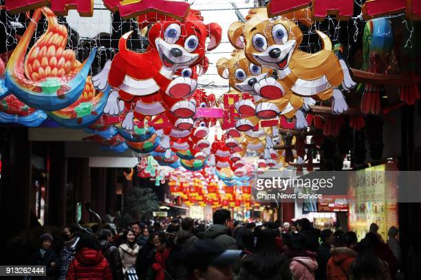 Tourists visit Yu Garden decorated with beautiful lanterns of dragons and phoenix before the arrival of the Year of the Dog on February 1 2018 in...