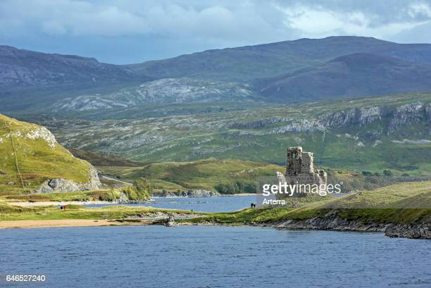 Tourists visiting 16th century Ardvreck Castle ruin at Loch Assynt in the Scottish Highlands Sutherland Scotland UK