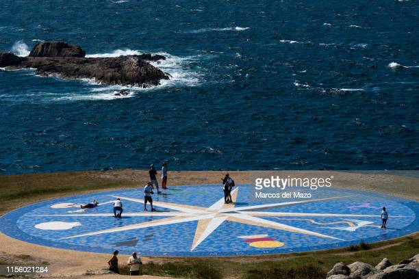 Tourists visiting a compass rose near The Tower of Hercules during a hot summer day