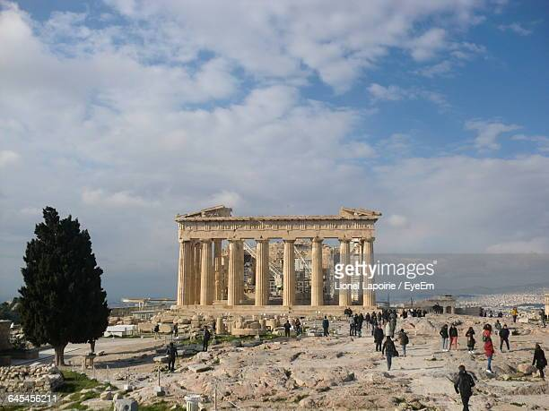 Tourists Visiting Acropolis Of Athens Against Sky