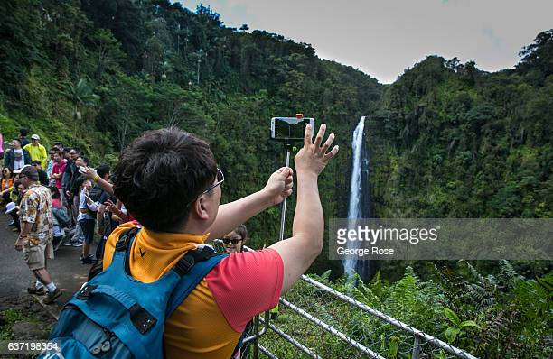 Tourists visiting Akaka Falls take selfies and pictures at the popular tourist lookout on December 14 near Honomu, Hawaii. Hawaii, the largest of all...