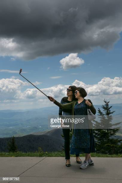 Tourists visiting Clingmans Dome a major scenic viewing point near the Appalachian Trail take a selfie on May 11 2018 near Cherokee North Carolina...