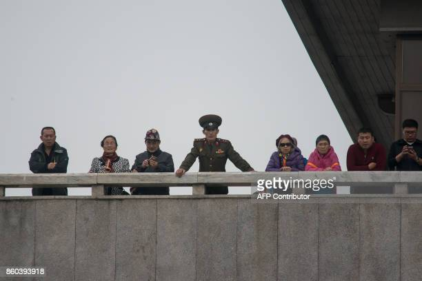 Tourists visiting North Korea stand on a balcony of Panmon hall on the North side of the military demarcation line separating North and South Korea...