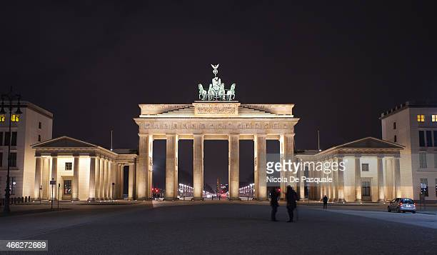 Tourists visiting the Brandenburg Gate at night. This monument is a former city gate, rebuilt in the late 18th century as a neoclassical triumphal...