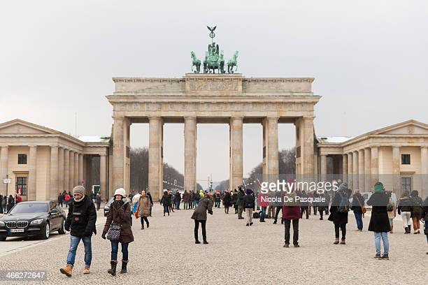 Tourists visiting the Brandenburg Gate . This monument is a former city gate, rebuilt in the late 18th century as a neoclassical triumphal arch, and...