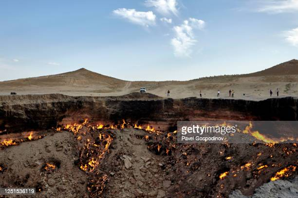tourists visiting the burning darvaza gas crater at sunset, turkmenistan - トルクメニスタン ストックフォトと画像