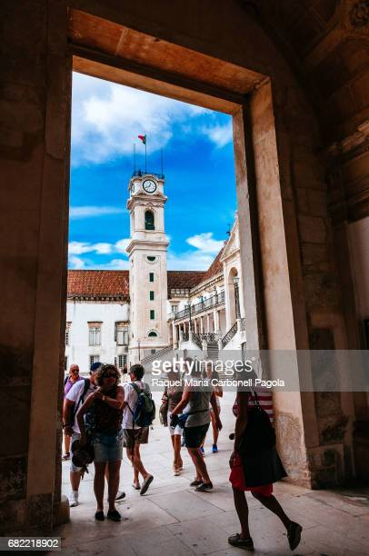Tourists visiting the forecourt of University of Coimbra in which the Joanine Library the University Tower and the statue of Joao III are placed