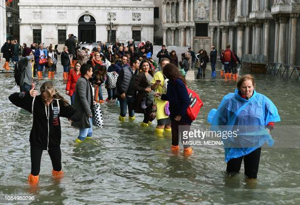 Tourists wade through water in the flooded St Mark Square during a highwater alert in Venice on October 29 2018 The flooding caused by a convergence...