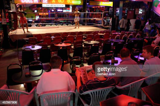 Tourists wait for a Thai boxing bout to start at an empty bar on Walking Street in Pattaya Pattaya is a seaside resort city a couple of hours east of...
